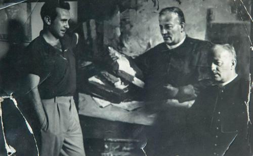 Dino Ferrari osserva il ritratto a Mons. Giuseppe Castelli, parroco del Sacro Cuore di Ascoli Piceno in presenza dello stesso, anni 50